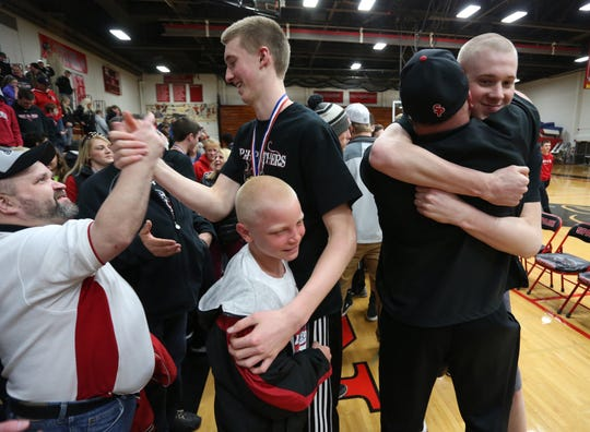 Brothers Sam Hauser (center) and Joey Hauser get congratulated by fans at Stevens Point Area Senior High School, March 22, 2015, as the team and fans celebrated their WIAA Division 1 boys' state basketball championship.
