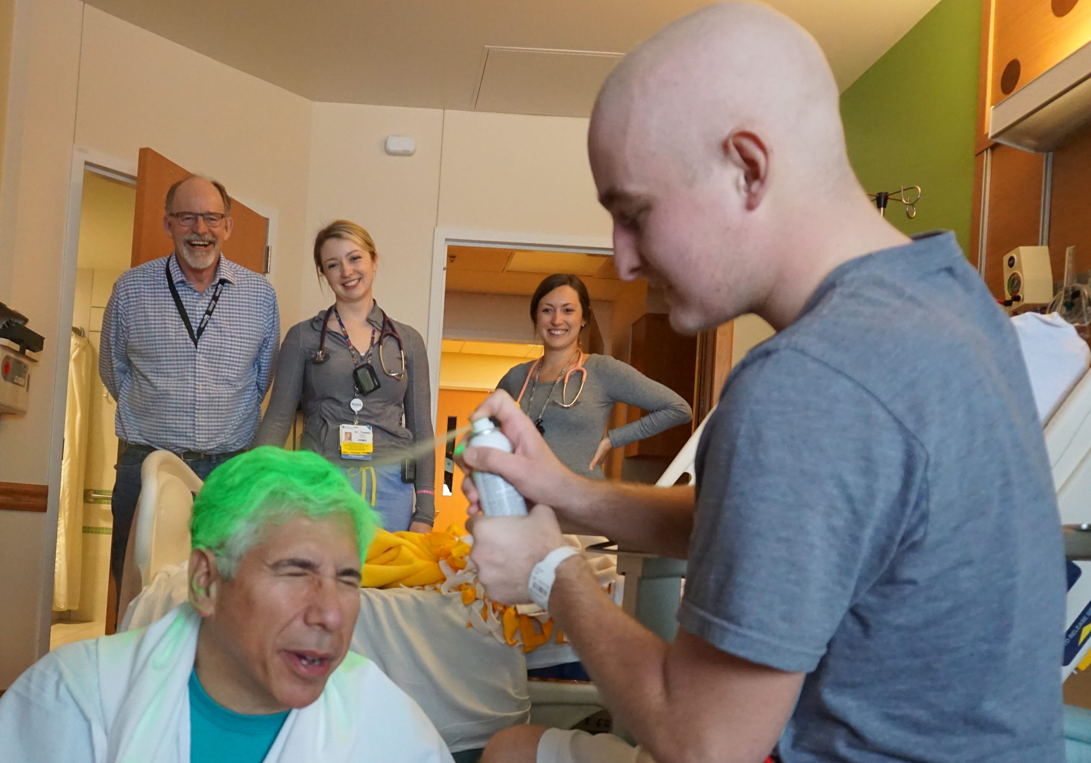 Patient Conner Lee sprays green dye on the hair of Dr. David Margolis of Children's Hospital of Wisconsin. The doctor allows patients to spray his hair green to support the Milwaukee Bucks during the NBA playoffs.