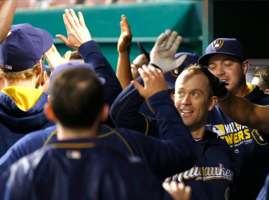 Milwaukee Brewers third baseman Aaron Hill (right) is congratulated by teammates after he hit a grand slam against the Cincinnati Reds during the tenth inning at Great American Ball Park on May 7, 2016. The Brewers won in ten innings 13-7.