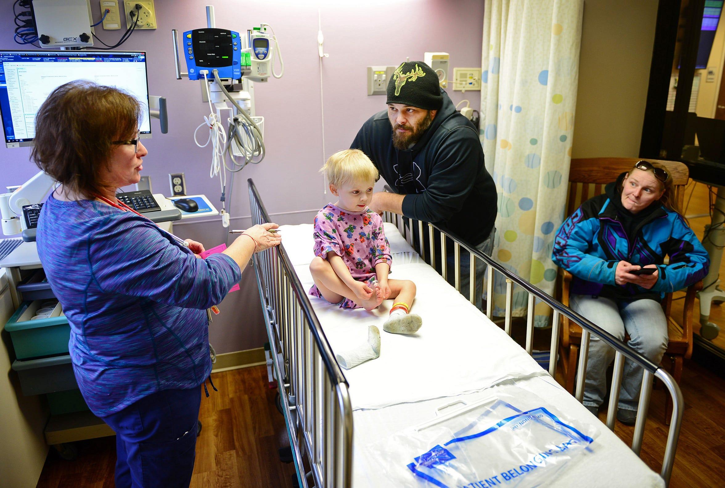 Nurse Kelli Kaminski checks in on BrentLee Van Haren during a follow-up care visit to Children's Hospital of Wisconsin on Feb. 7. His father, Robert, is beside him. Seated is BrentLee's mom, Chelsey Meverden.