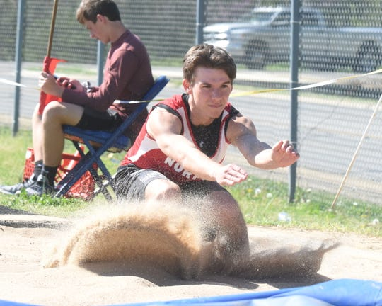 Norfork's Bryson Thiel lands in the triple jump on Monday.