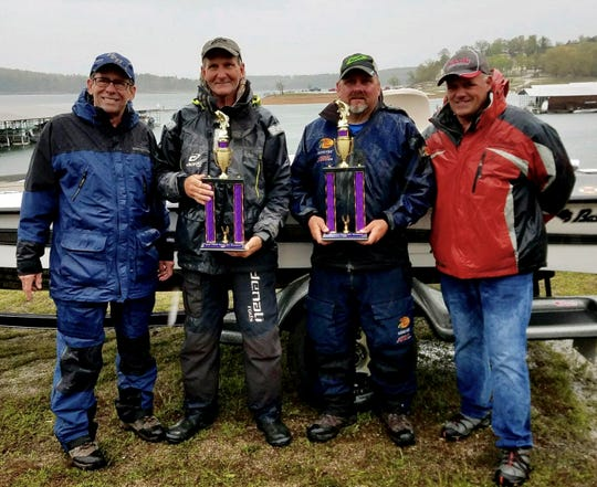Ty Bowman and Verlin Cotter hold their trophies after winning the 34th annual Cystic Fibrosis Benefit Bass Tournament on Norfork Lake. Pictured with Bowman and Cotter are tournament director Dan Singletary (left) and Rick Pierce of BassCat Boats (right). The duo won a BassCat Margay Vision boat and trailer and $1,000.