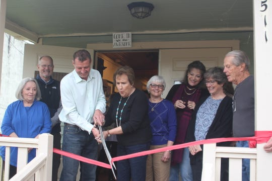 Roger Podwoski, president of the Cotter-Gassville Chamber of Commerce, helps gallery owner Marilyn Morris cut the ribbon at the grand opening of the River Art Gallery in Cotter on April 13. The gallery is located at 511 Second Street, across from the post office.