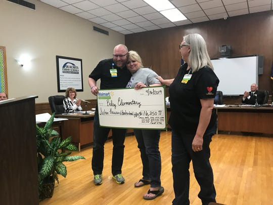 Representatives from WalMart Neighborhood Markets (far left and far right) presented a check for Boley Elementary School to Principal Sandy Bates on Tuesday at the Ouachita Parish School Board meeting.