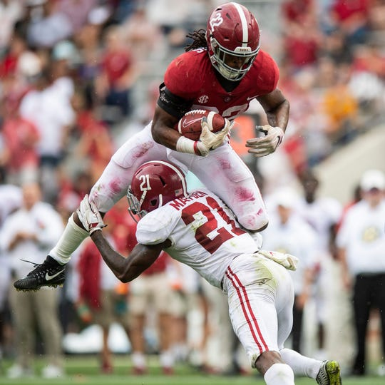 Running back Najee Harris (22) tries to hurdle defensive back Jared Mayden (21) during second half action in the Alabama A-Day spring football scrimmage game at Bryant Denny Stadium in Tuscaloosa, Ala., on Saturday April 13, 2019.