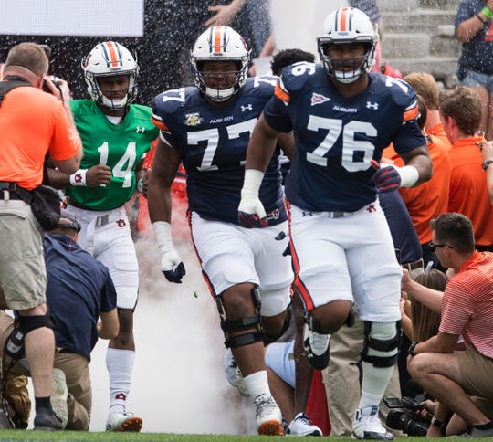 Auburn offensive lineman Marquel Harrell (77) and offensive lineman Prince Tega Wanogho (76) take the field before the A-Day spring game at Jordan-Hare Stadium in Auburn, Ala., on Saturday, April 13, 2019.