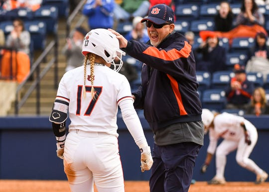 Auburn softball player Morgan Podany (No. 17) receives a pat on the head.