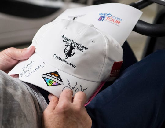 Golfer Jason Bohn autographs hats for fellow heart attack survivors at the Normandie Medical Building in Montgomery, Ala., on Tuesday, April 16, 2019. Bohn suffered a heart attack at a golf tournament in 2016.
