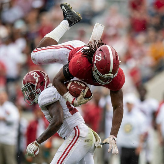 Running back Najee Harris (22) is upended by defensive back Jared Mayden (21) during second half action in the Alabama A-Day spring football scrimmage game at Bryant Denny Stadium in Tuscaloosa, Ala., on Saturday April 13, 2019.