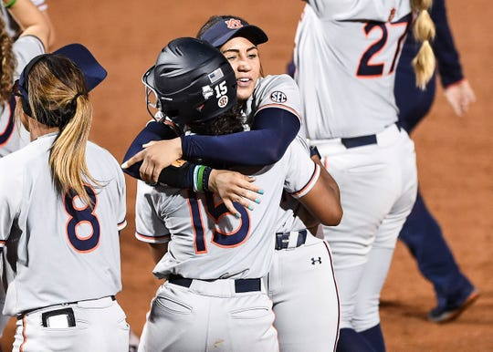 Auburn outfielder Bree Fornis (No. 15) receives a hug from a softball teammate.