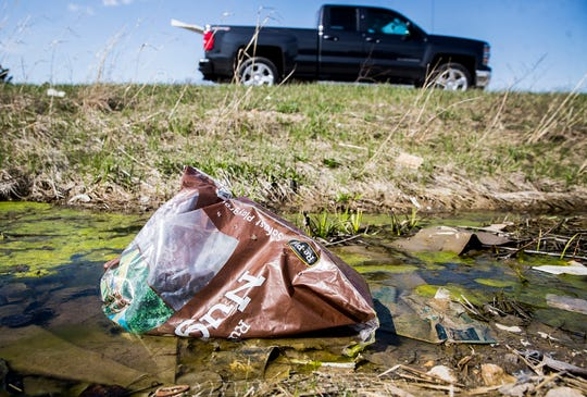 Litter collects along most of the grassy median between McGalliard Road and Bethel Avenue.