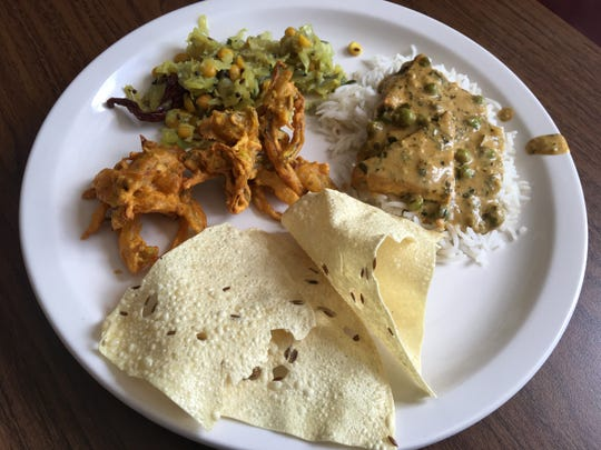 Royal Indian Cuisine's buffet items, from left, vegetable pakora (onions, spinach and potatoes deep-fried in chickpea batter), cabbage puriyal; methi paneer, made with peas and cheese, served atop rice; and papadum (lentil crackers).