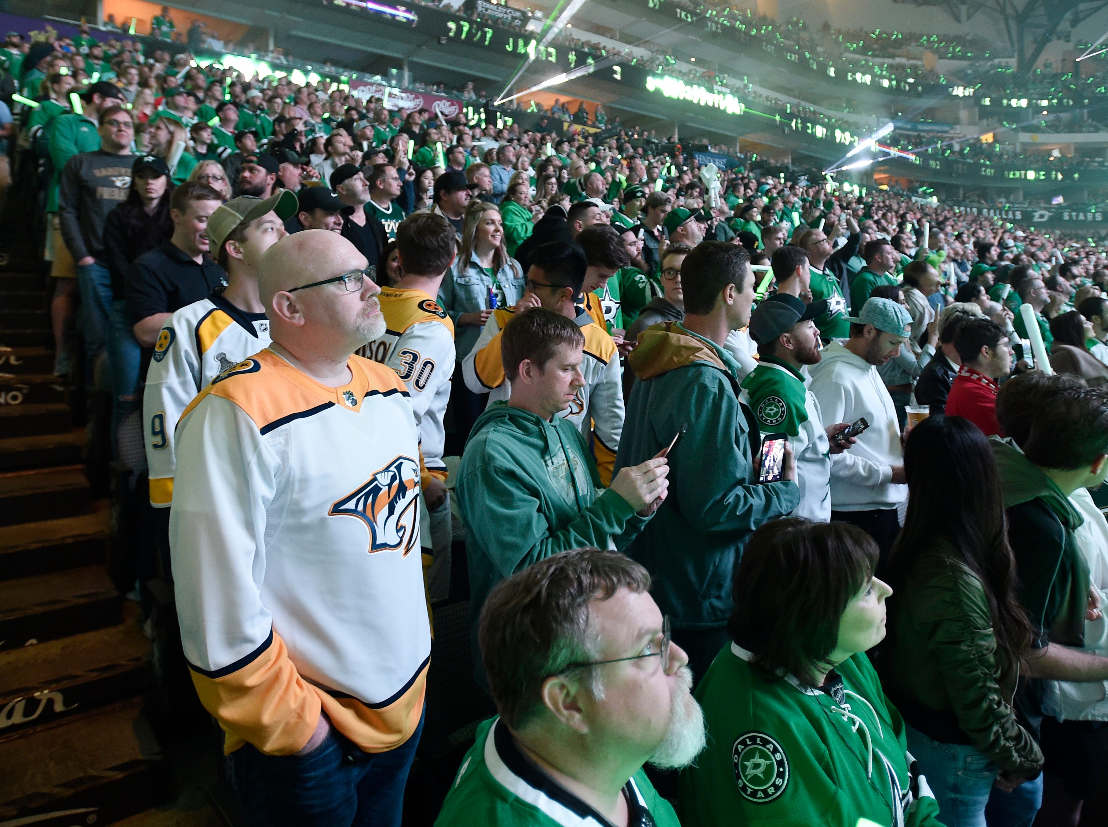 Predators fans surrounded by Stars fans wait for the start of the divisional semifinal game at the American Airlines Center in Dallas, Texas., Monday, April 15, 2019.