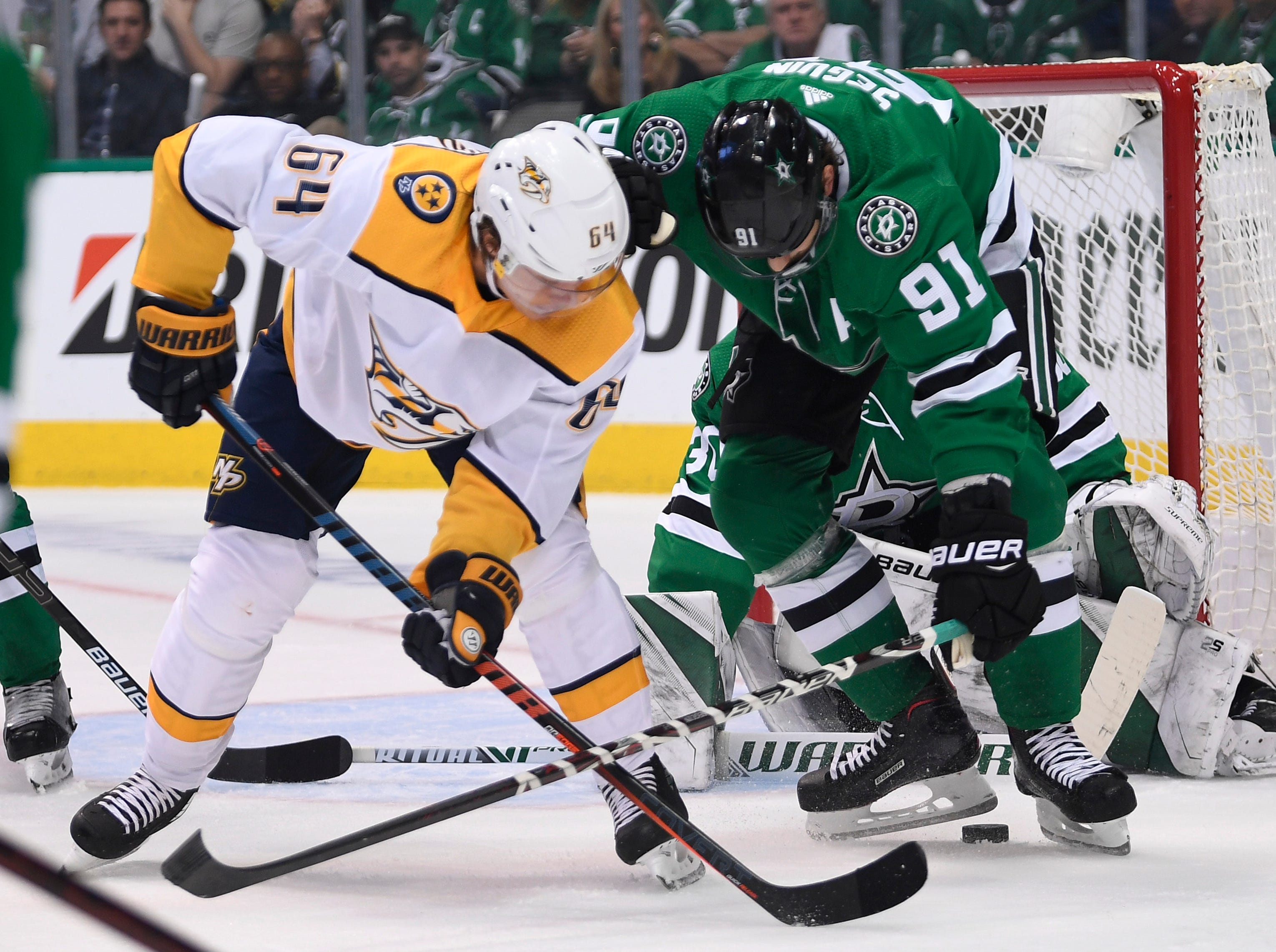 Nashville Predators center Mikael Granlund (64) tries to move the puck under Dallas Stars center Tyler Seguin (91) during the first period of the divisional semifinal game at the American Airlines Center in Dallas, Texas., Monday, April 15, 2019.