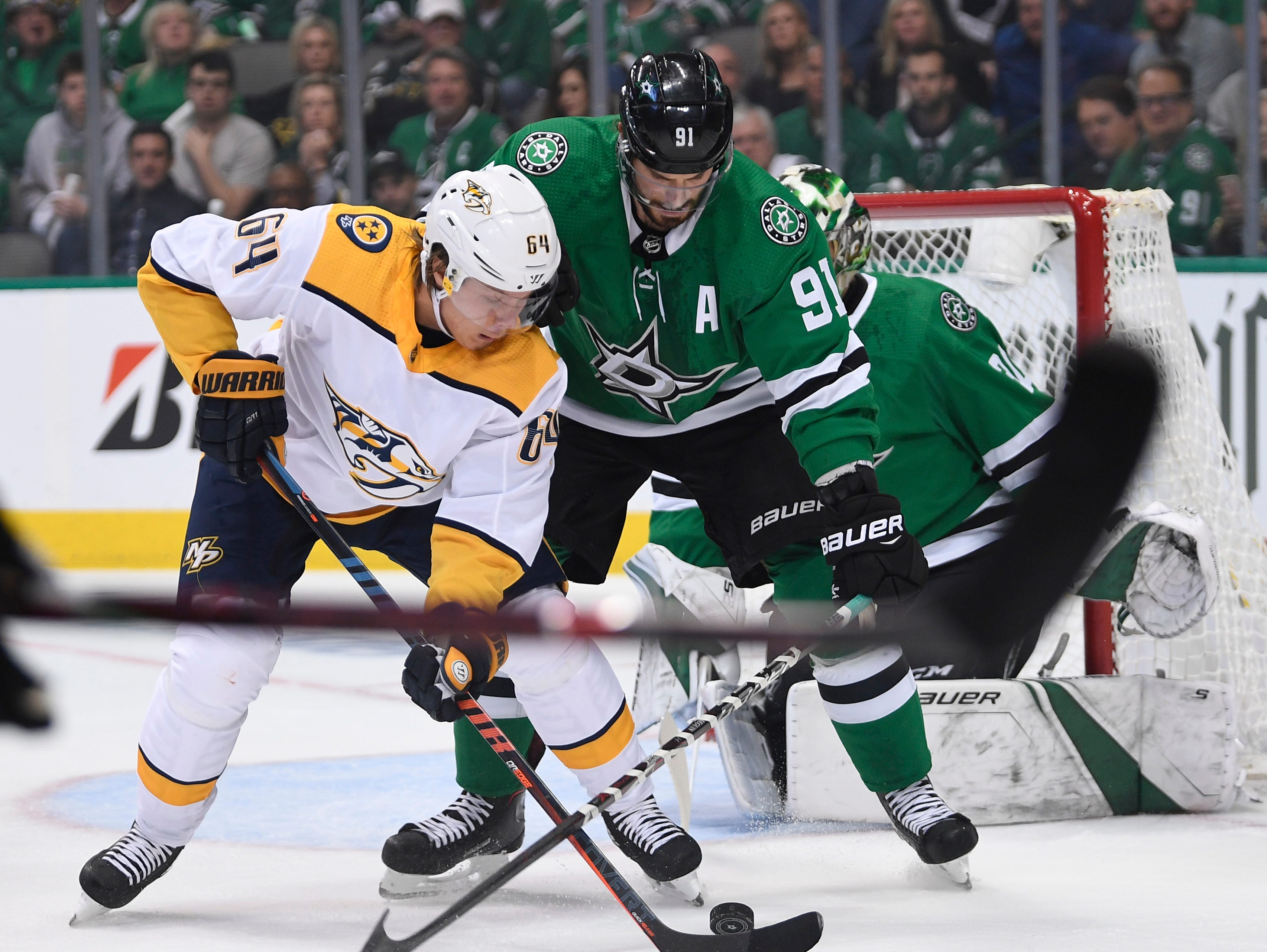 Nashville Predators center Mikael Granlund (64) moves the puck defended by Dallas Stars center Tyler Seguin (91) during the first period of the divisional semifinal game at the American Airlines Center in Dallas, Texas., Monday, April 15, 2019.