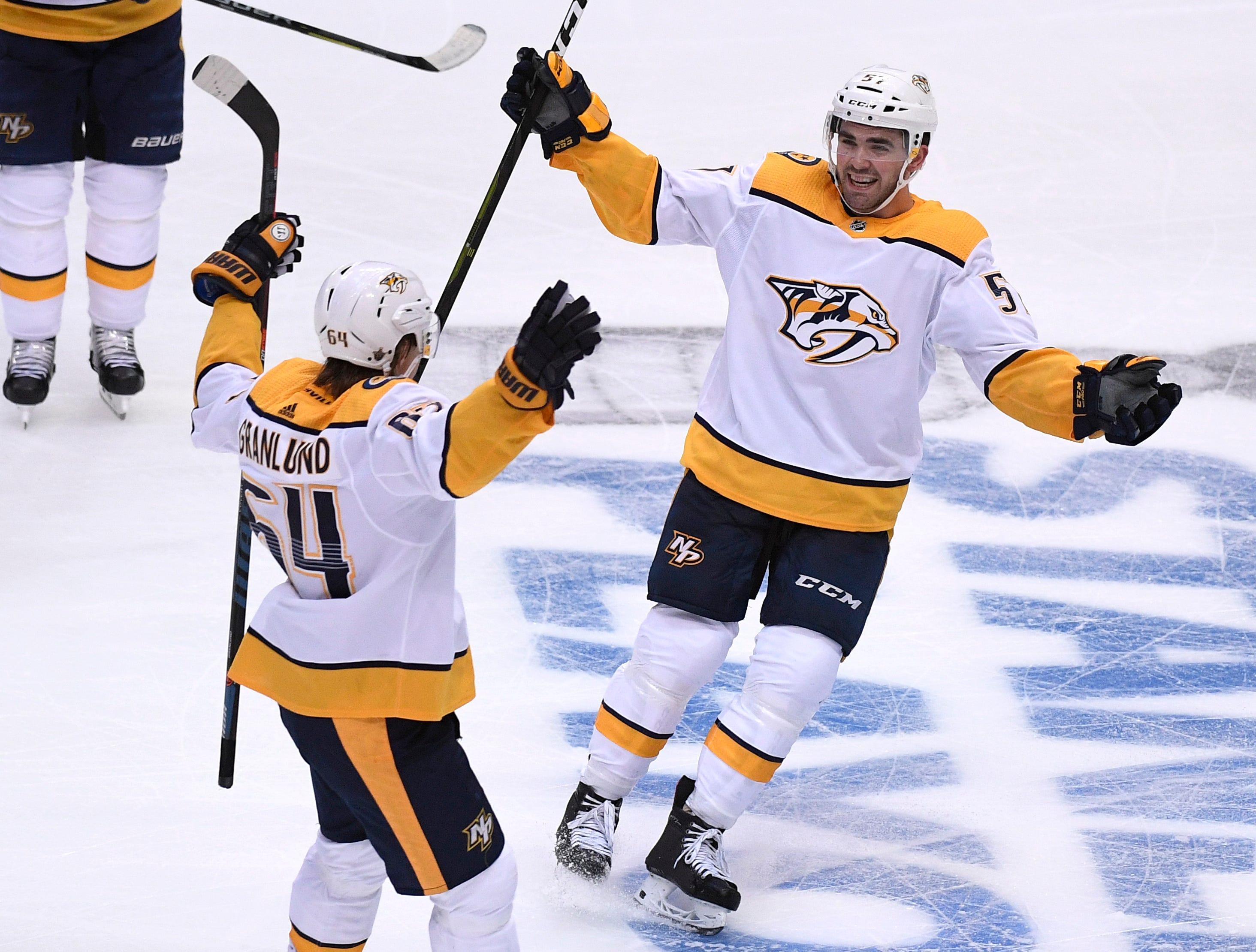 Nashville Predators center Mikael Granlund (64) celebrates his game winner with defenseman Dante Fabbro (57) during the third period of the divisional semifinal game at the American Airlines Center in Dallas, Texas., Monday, April 15, 2019.