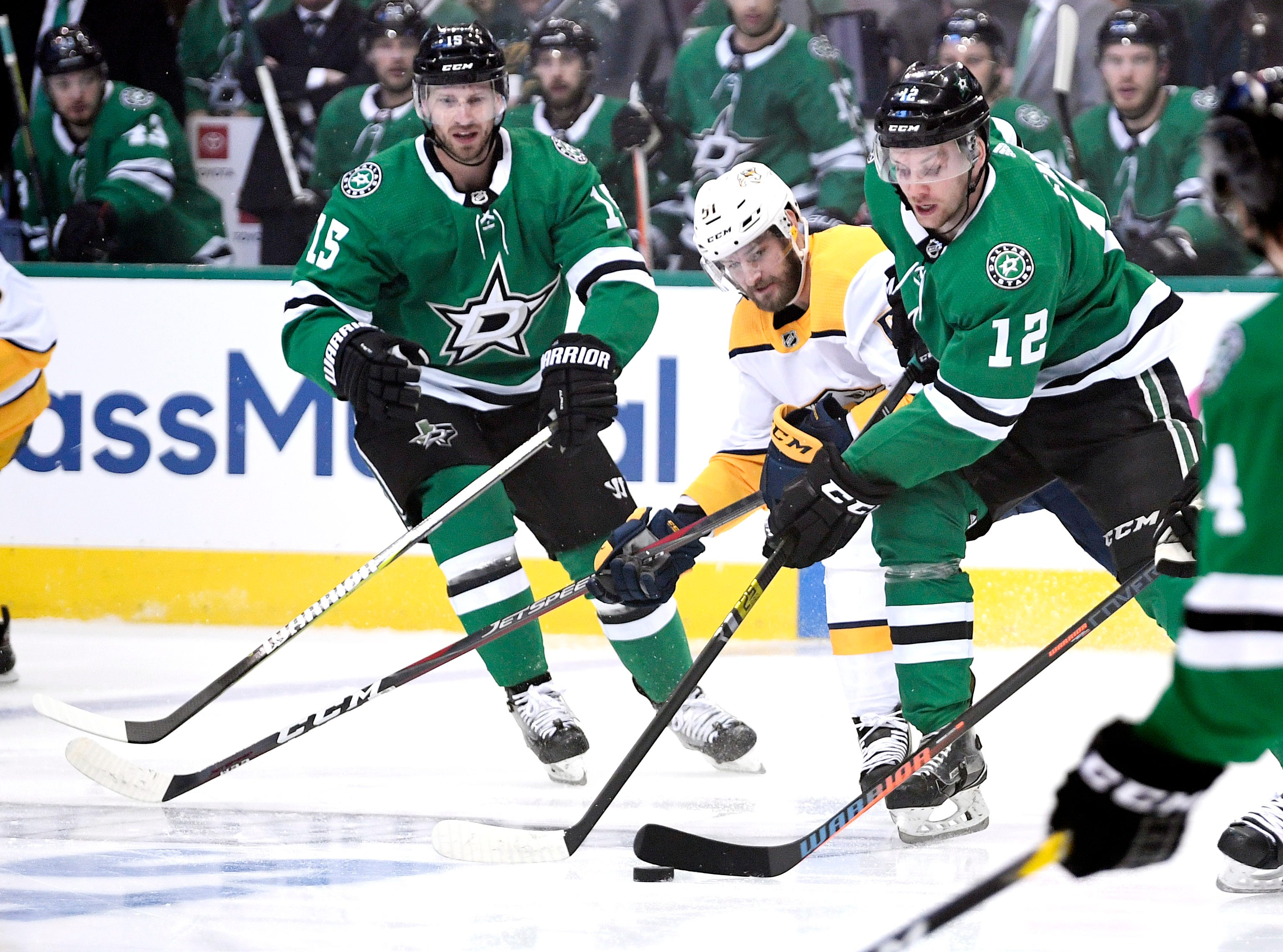 Dallas Stars center Radek Faksa (12) moves the puck defended by Nashville Predators left wing Austin Watson (51) during the first period of the divisional semifinal game at the American Airlines Center in Dallas, Texas., Monday, April 15, 2019.