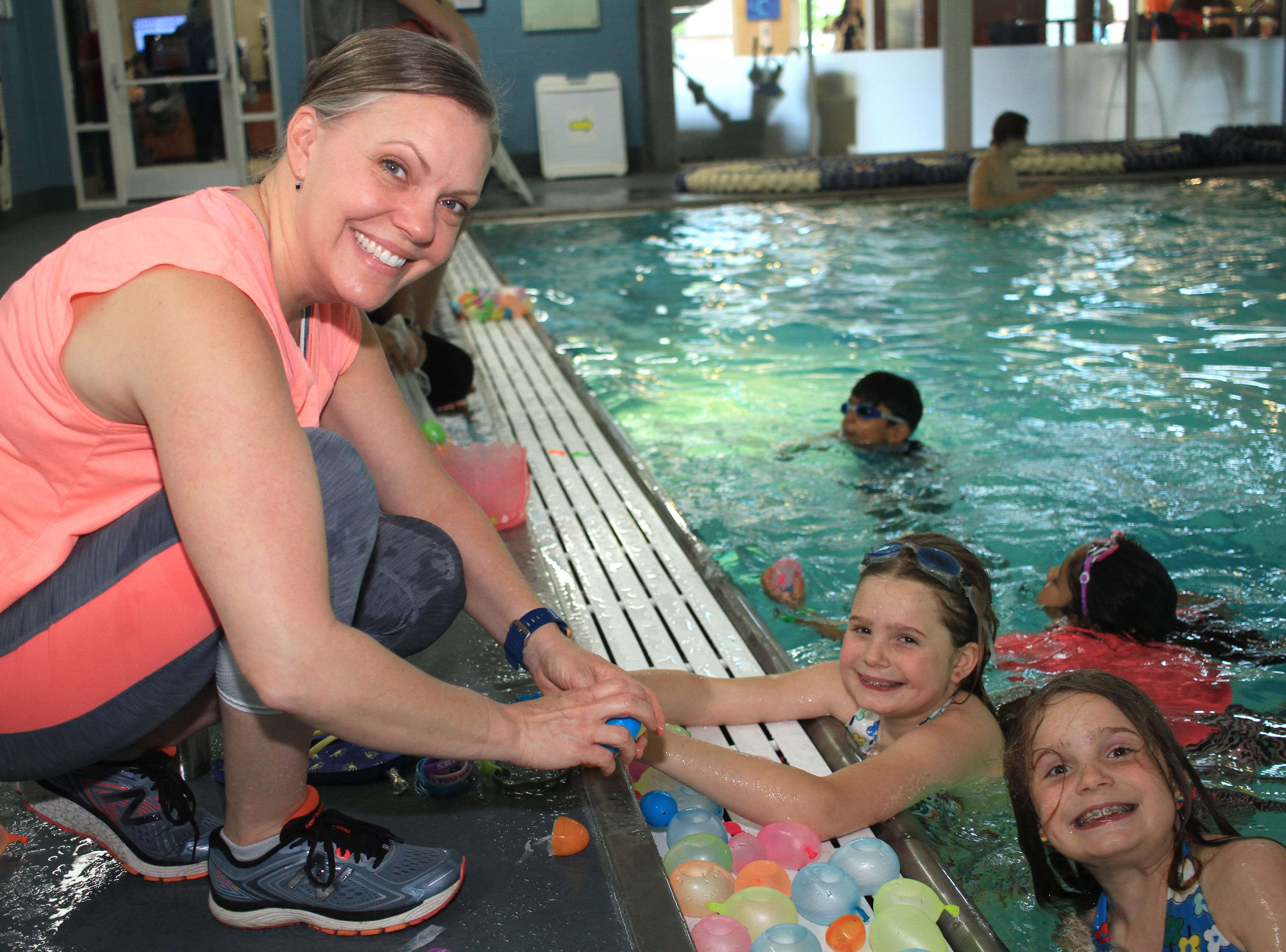 Jennifer Zehnder helps her twins Evenly and Abigail haul in their eggs at an Easter egg hunt in the pool at the Sumner County YMCA in Hendersonville, TN on Saturday, March 13, 2019.