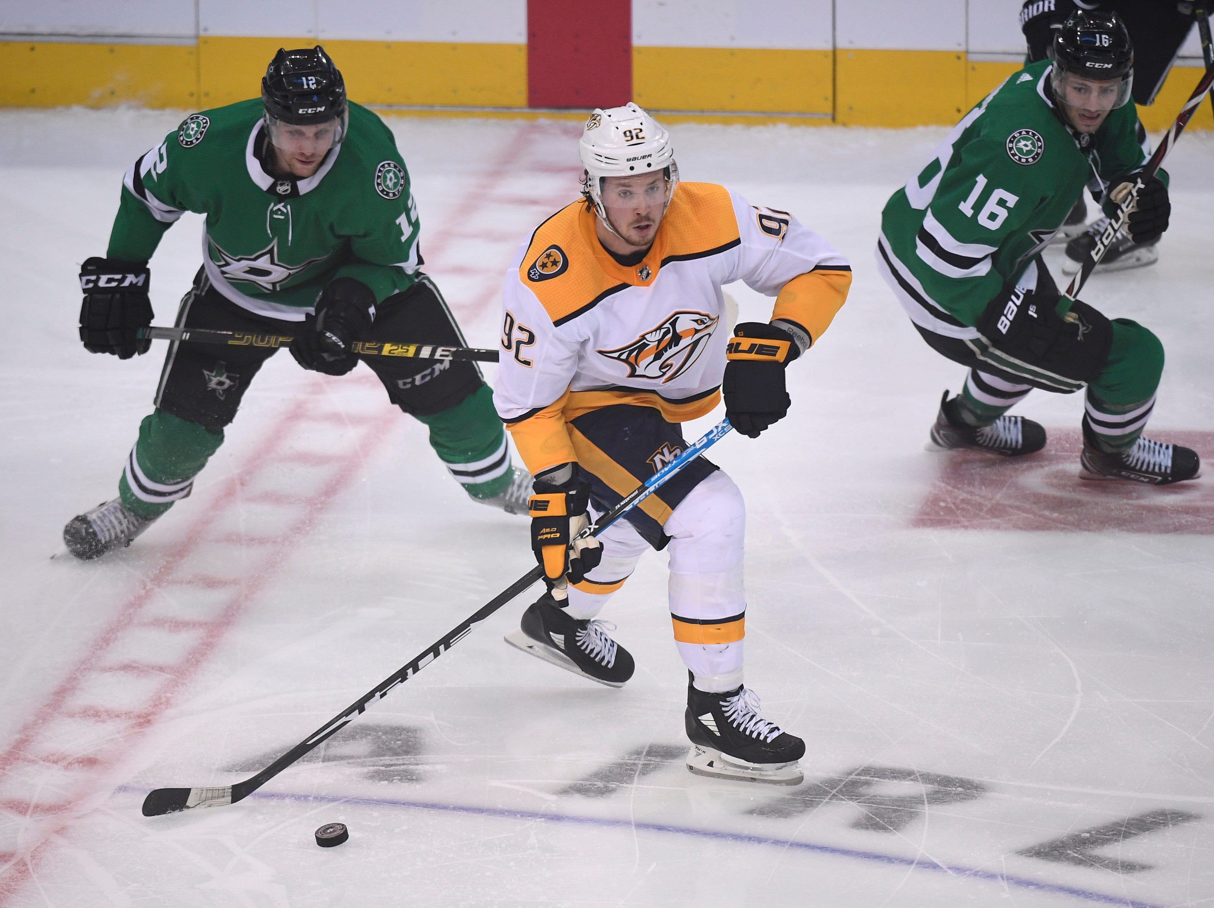 Nashville Predators center Ryan Johansen (92) moves the puck trailed by Dallas Stars centers Radek Faksa (12) and Jason Dickinson (16) during the third period of the divisional semifinal game at the American Airlines Center in Dallas, Texas., Monday, April 15, 2019.