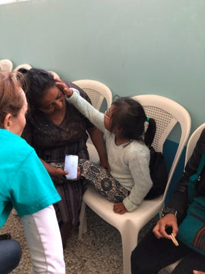 A little girl touches her mom's face after receiving a pair of glasses through Sumner County medical mission trip workers.