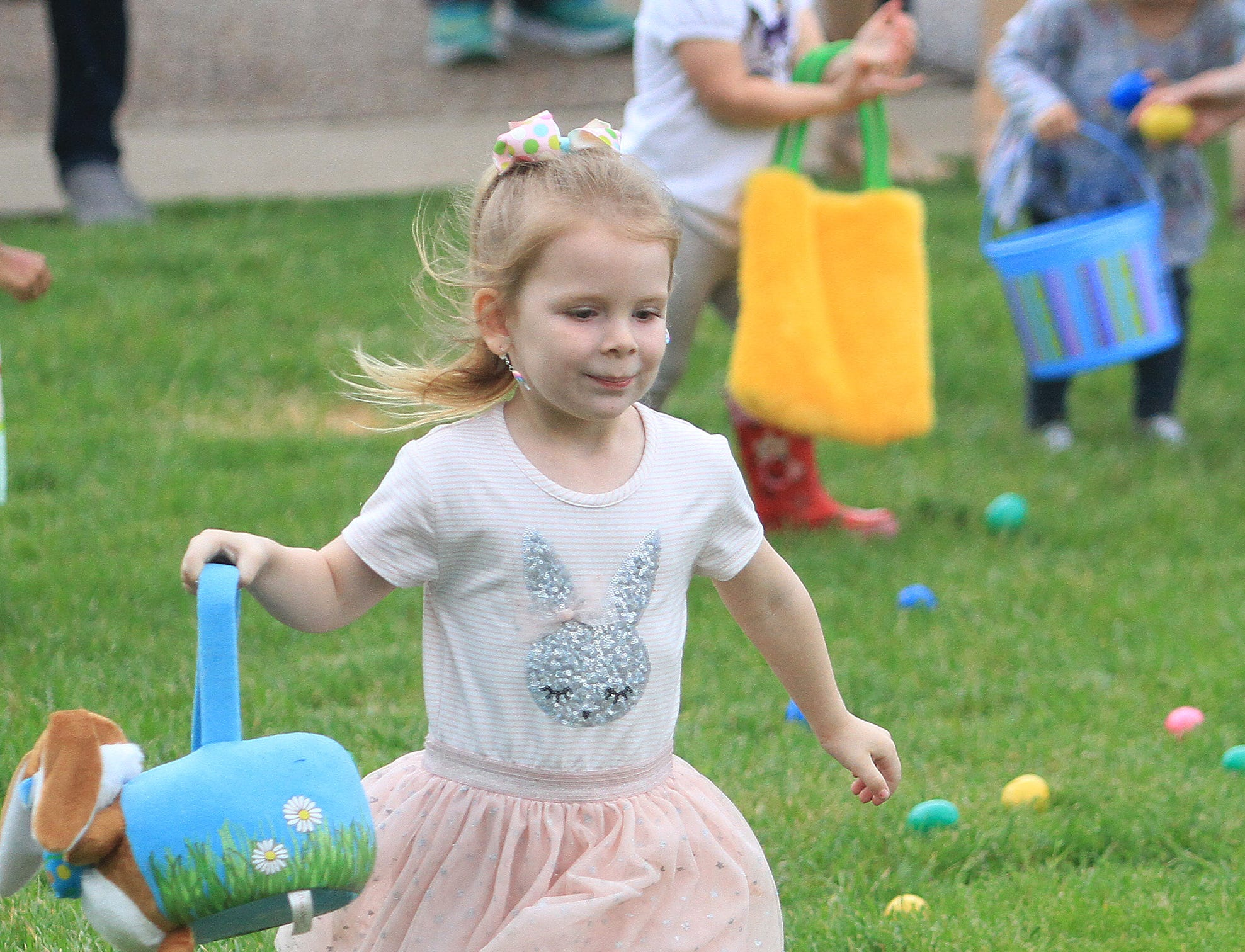 A young girl runs with her basket at the Egg hunt at the Sumner County YMCA in Hendersonville, TN on Saturday, April 13, 2019.