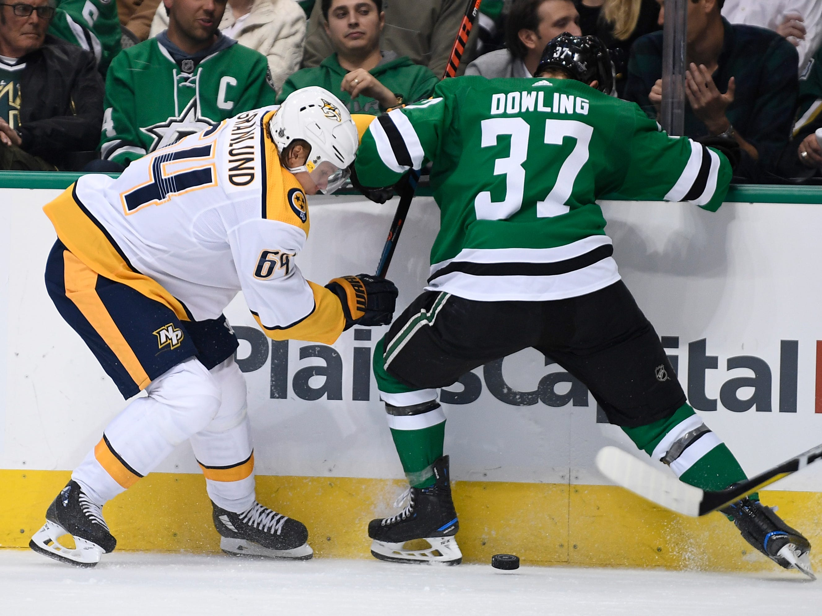 Nashville Predators center Mikael Granlund (64) and Dallas Stars center Justin Dowling (37) battle for the puck along the boards during the second period of the divisional semifinal game at the American Airlines Center in Dallas, Texas., Monday, April 15, 2019.