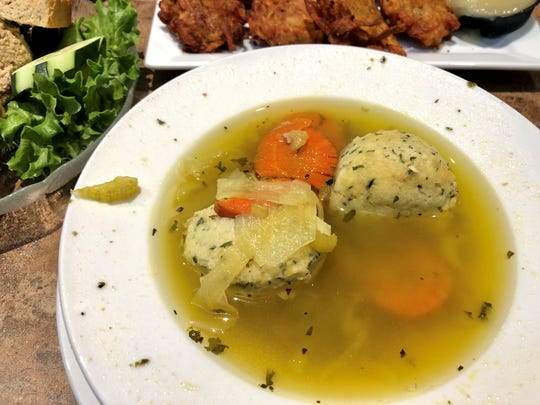 Matzo ball soup shimmering with chicken-y goodness from Toojay's Deli at Mercato.