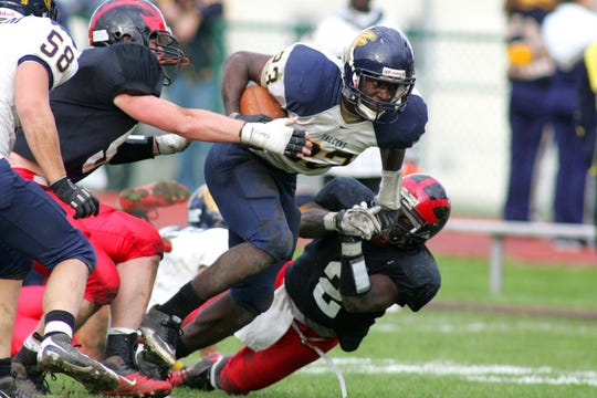 Saddle Brook running back Steve Longa (#23) breaks through the tackle attempts of Glen Rock defenders during a 2010 game.