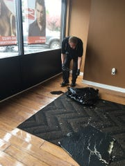 Michael Morea, co-owner of Sara Michael Hair Salon, inspects broken ceiling tiles that fell from the ceiling due to water damage. It's the second time the business had to close due to the aftereffects of a fallen facade at the Kress Plaza strip mall last year.