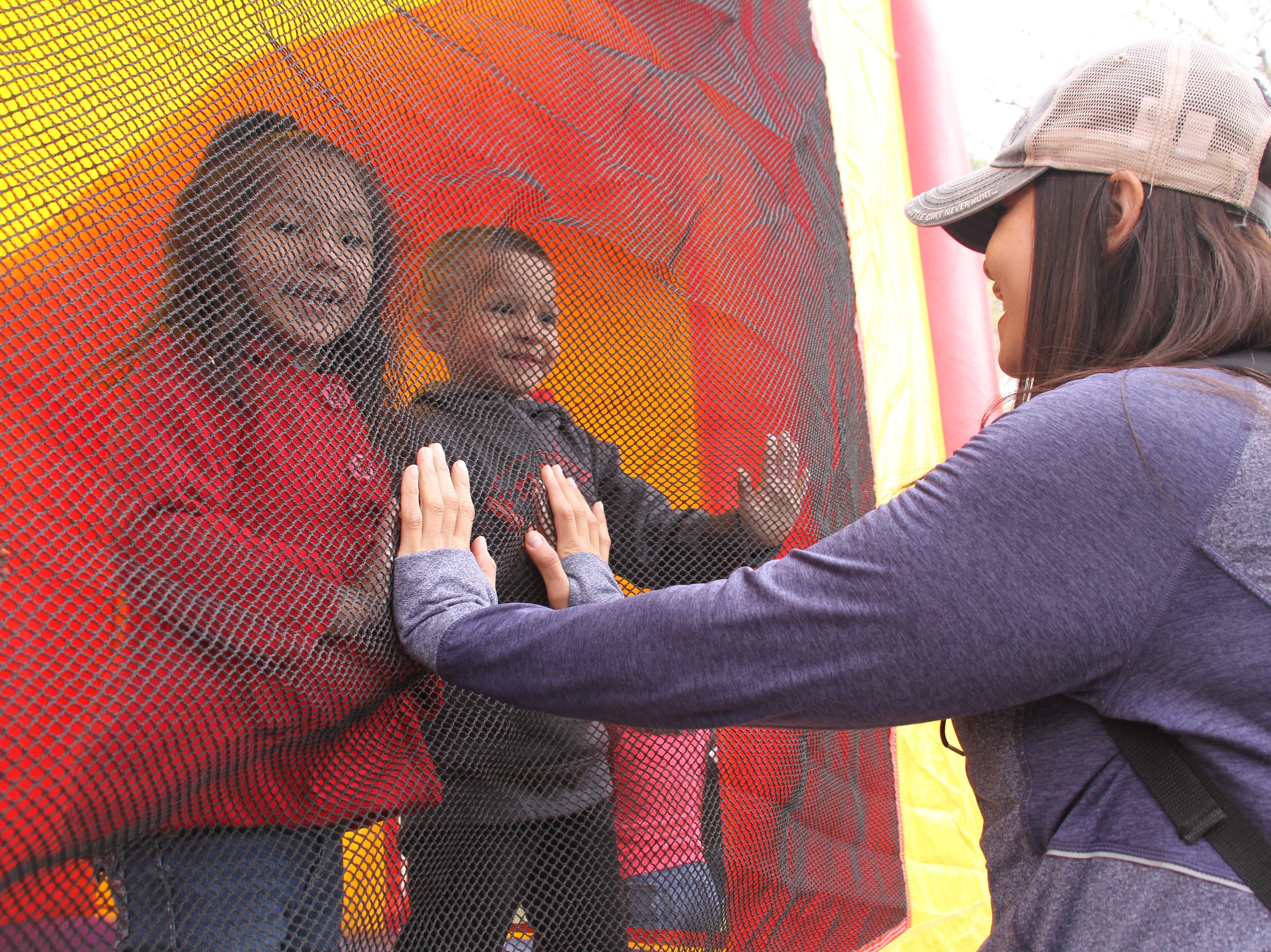 Christina Benzor has her children, Ali Enciso, 5, and Luis Jara, 5, meet her hands as they jump in the inflatable bounce house.
