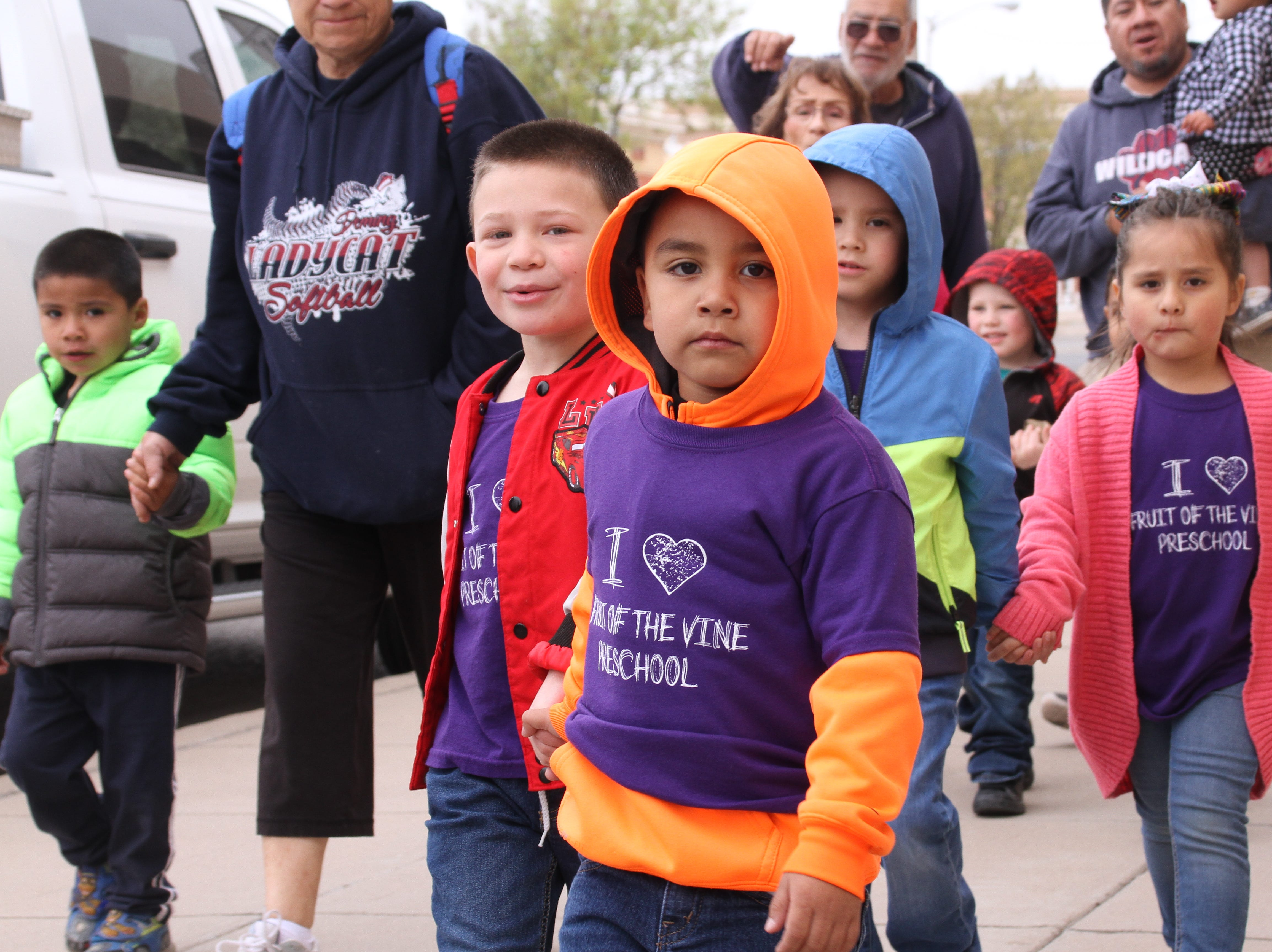 Five-year-old Santiago Villa of Fruit of the Vine preschool leads his classmates during the Childhood Abuse Awareness walk.