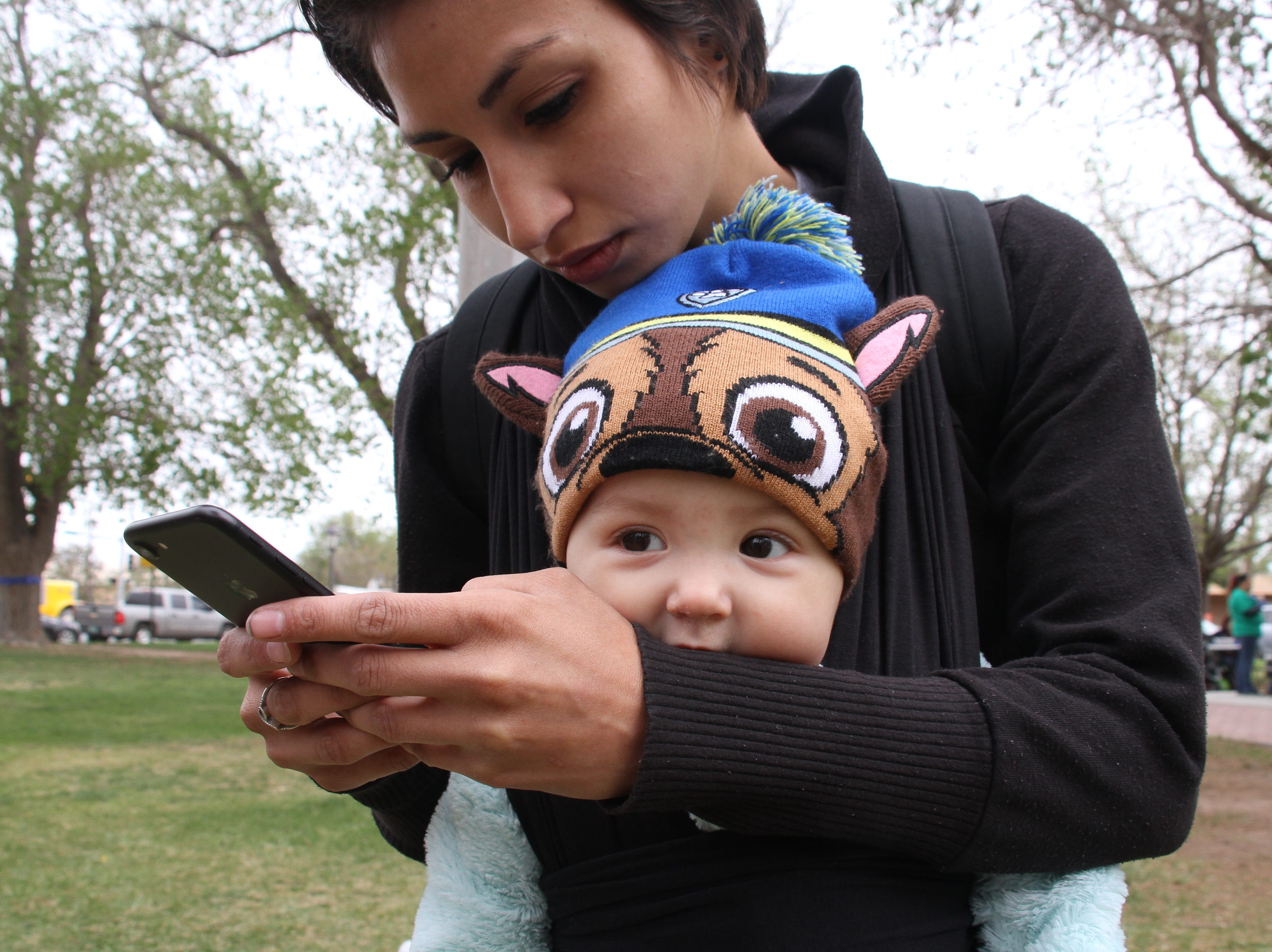 Ingrid Gonzalez on phone while 8-month-old Dzidziely Lucero sucks on her mother's sleeve.
