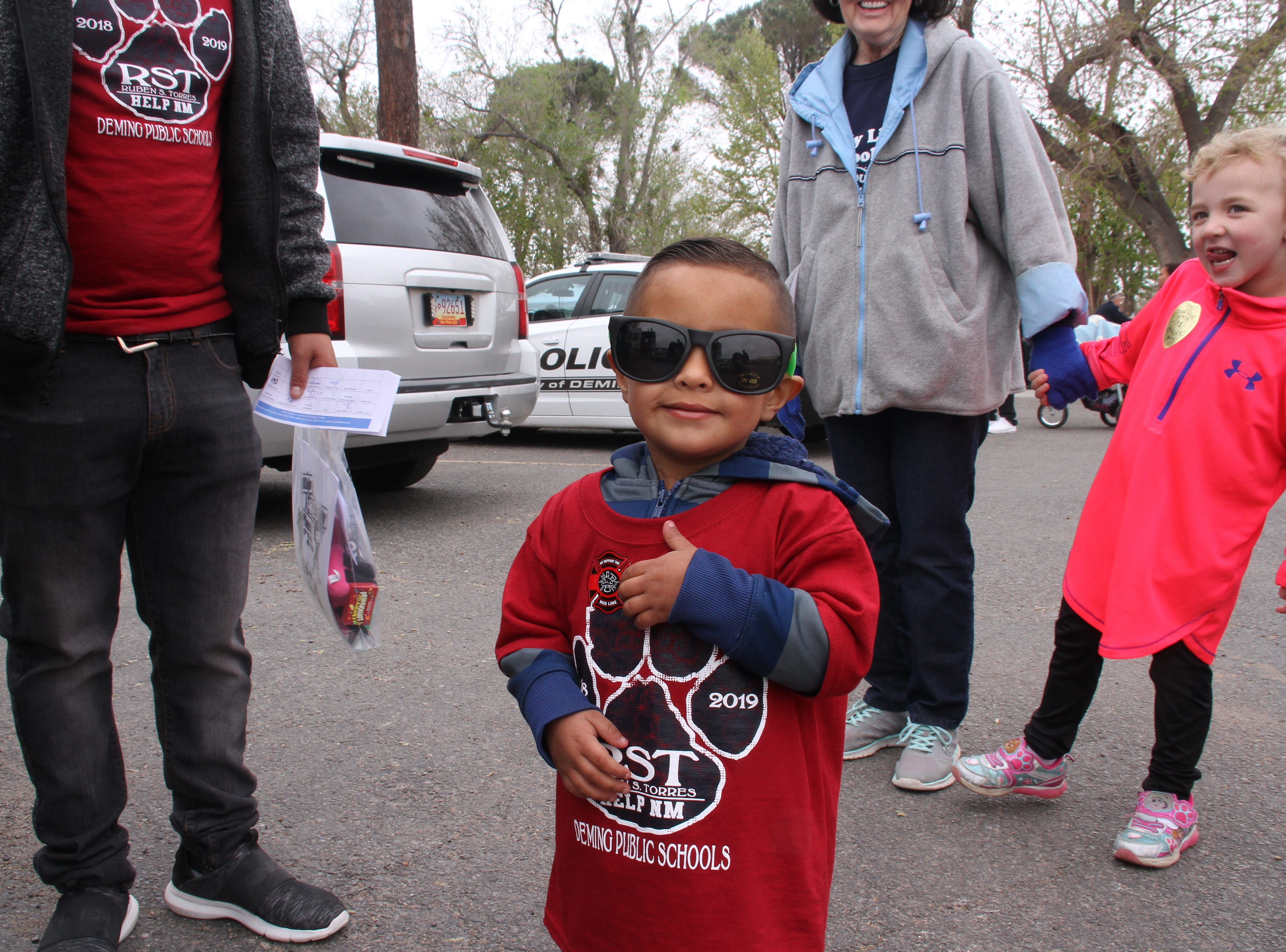 Three-year-old Ezequiel Peña looking cool with his over-sized sunglasses and a sticker badge.