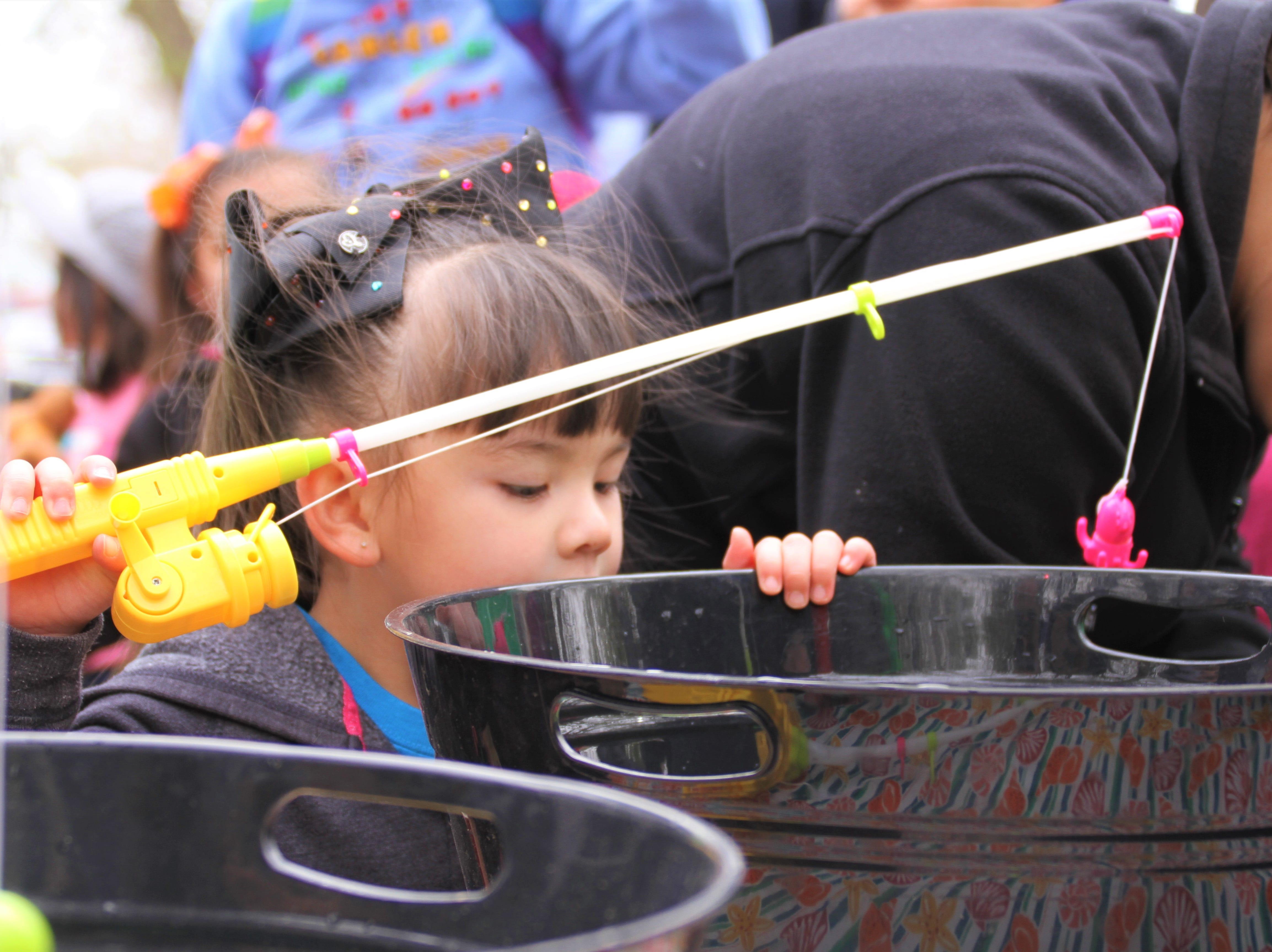 Three-year-old Alesandra Holguin peers  in into the bucket of water to get a better look and a better chance at catching a toy with her pretend fishing rod -- in hopes of winning a prize.