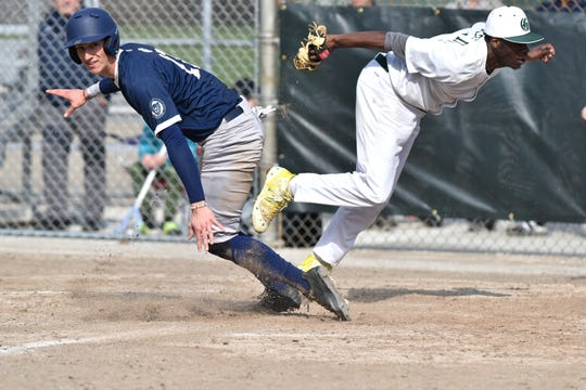 Detroit Country Day player Parker Pilat nearly collides with Groves pitcher Roger Motley III at homeplate - as Motley covers.