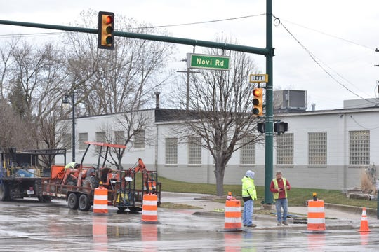 Orange barrels block off a lane of Novi Road near Main Street on April 16 as workers finish up closing a hole made in the pavement to re-direct a gas line under the surface.
