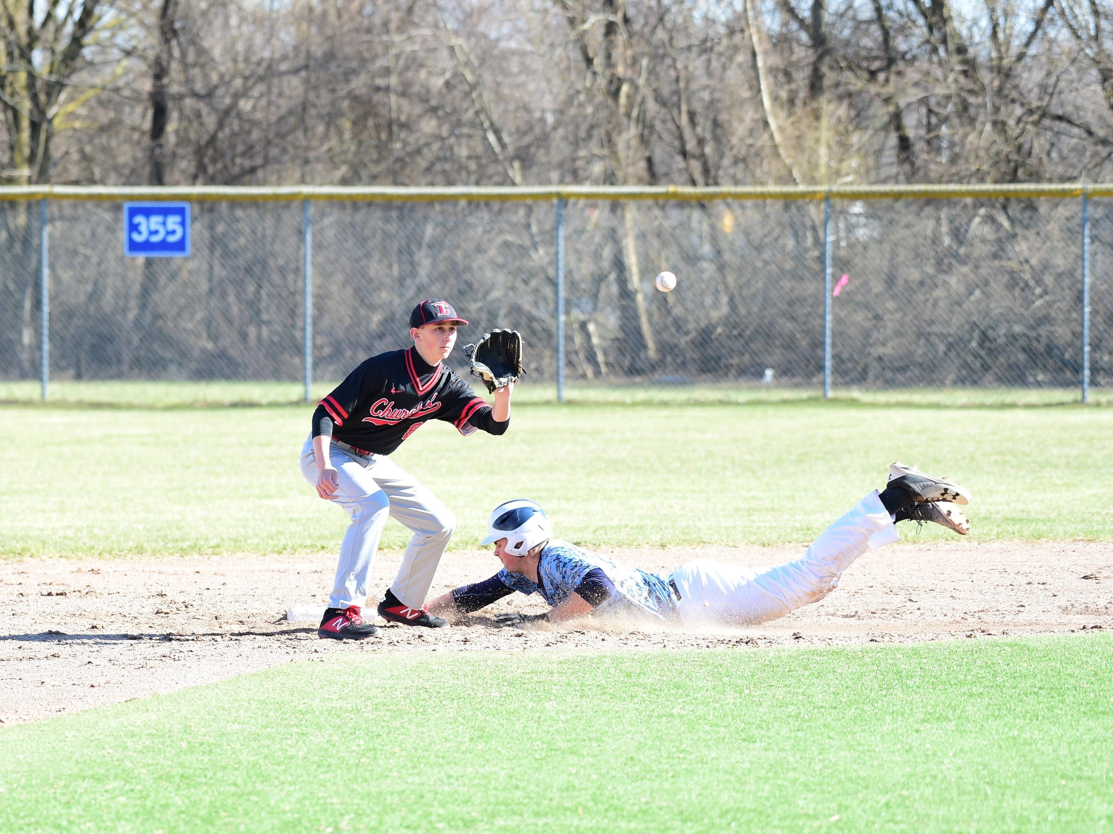 Livonia Churchill's Ryan Kennell goes to tag Stevenson's Nate Waligora in a game on April 15, 2019.