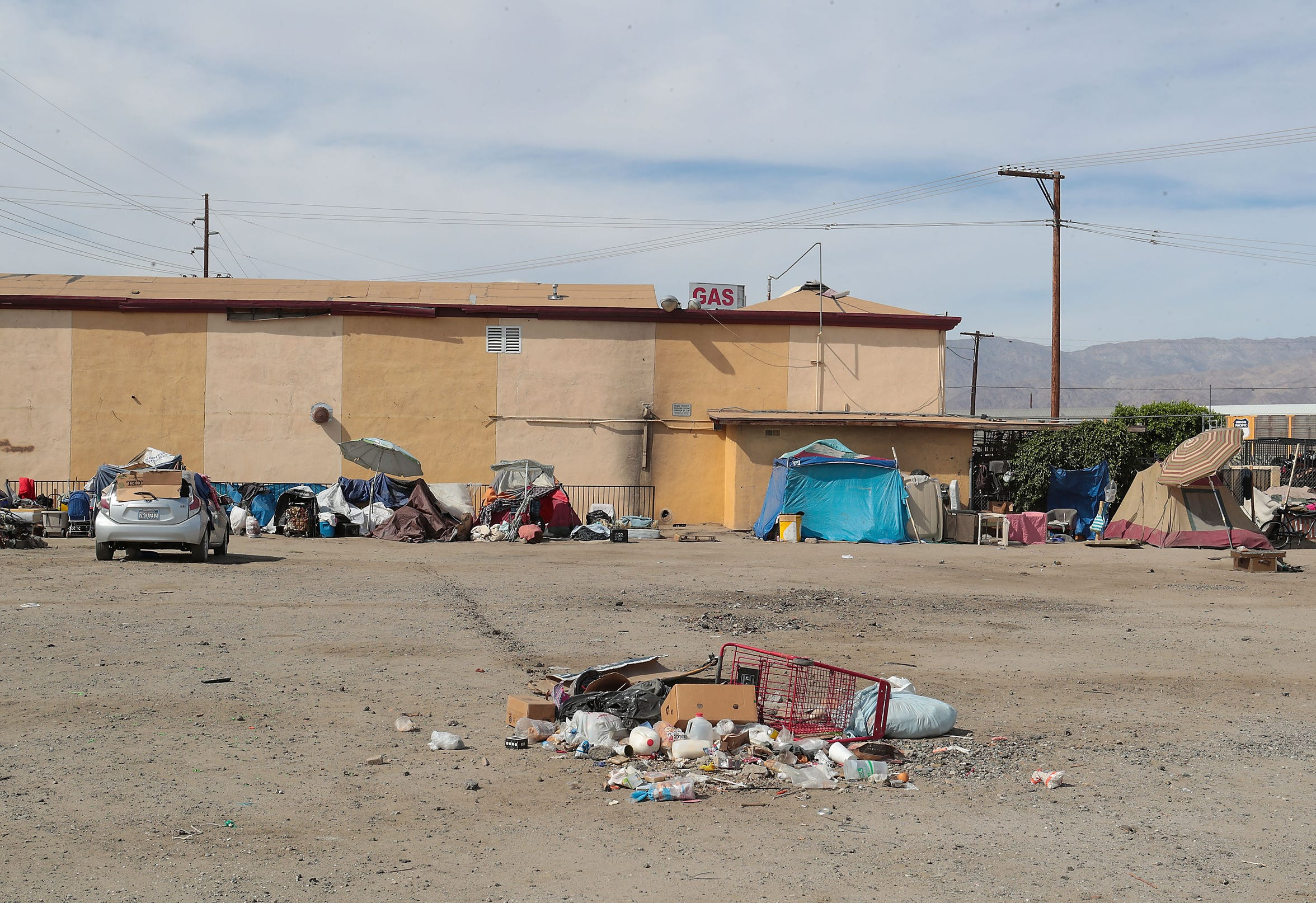 People experiencing homelessness have taken refuge in a large vacant lot near the intersection of Highway 111 and Van Buren St. in Indio, April 9, 2019.