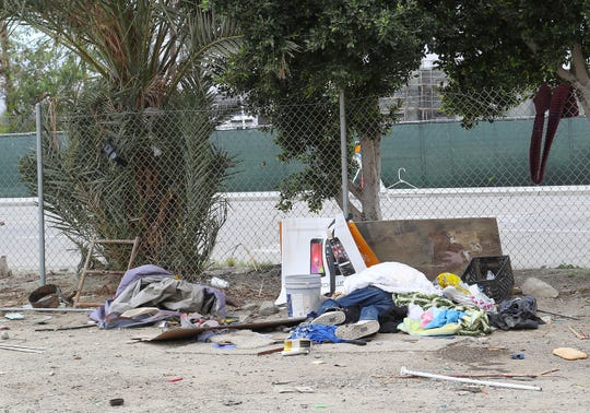 A person sleeps on the ground in a homeless camp behind the One Stop Shoppe in Indio, April 8, 2019.