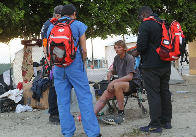 Some of the Coachella Valley Volunteers in Medicine talk with Robert Hensley while supplying medical care to some of the homeless living in a large camp in Indio, April 9, 2019.
