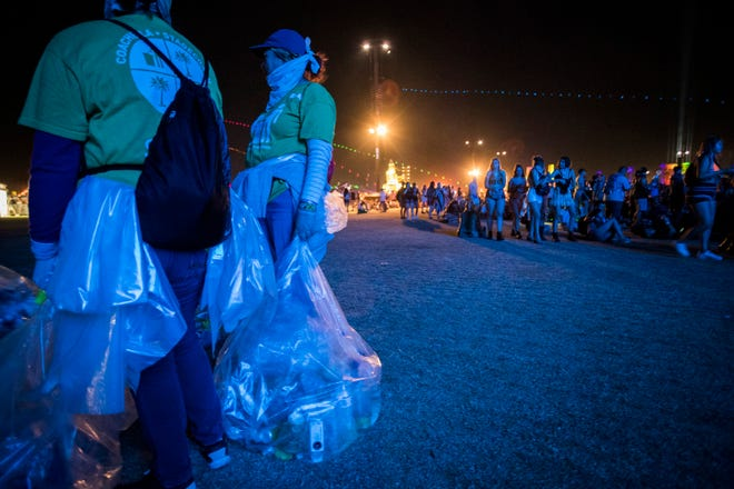 Workers pick up trash during the first weekend of the Coachella Valley Music and Arts Festival at the Empire Polo Club in Indio.