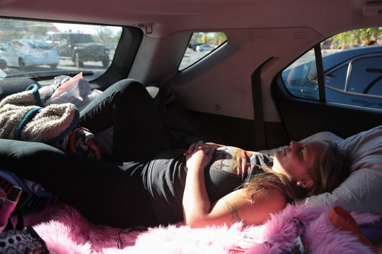 Jenny Hedstrom takes a nap in her car before starting to drive on Saturday evening during the first weekend of the Coachella Valley Music and Arts Festival, La Quinta, Calif., April, 13, 2019. She plans to live out of her car while driving duing the next three weekends of music festivals.