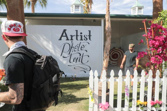 A man walks past the Artist Photo Tent of Andrew Haagen on Sunday, April 15, 2019 at the Coachella Valley Music and Arts Festival in Indio, Calif.