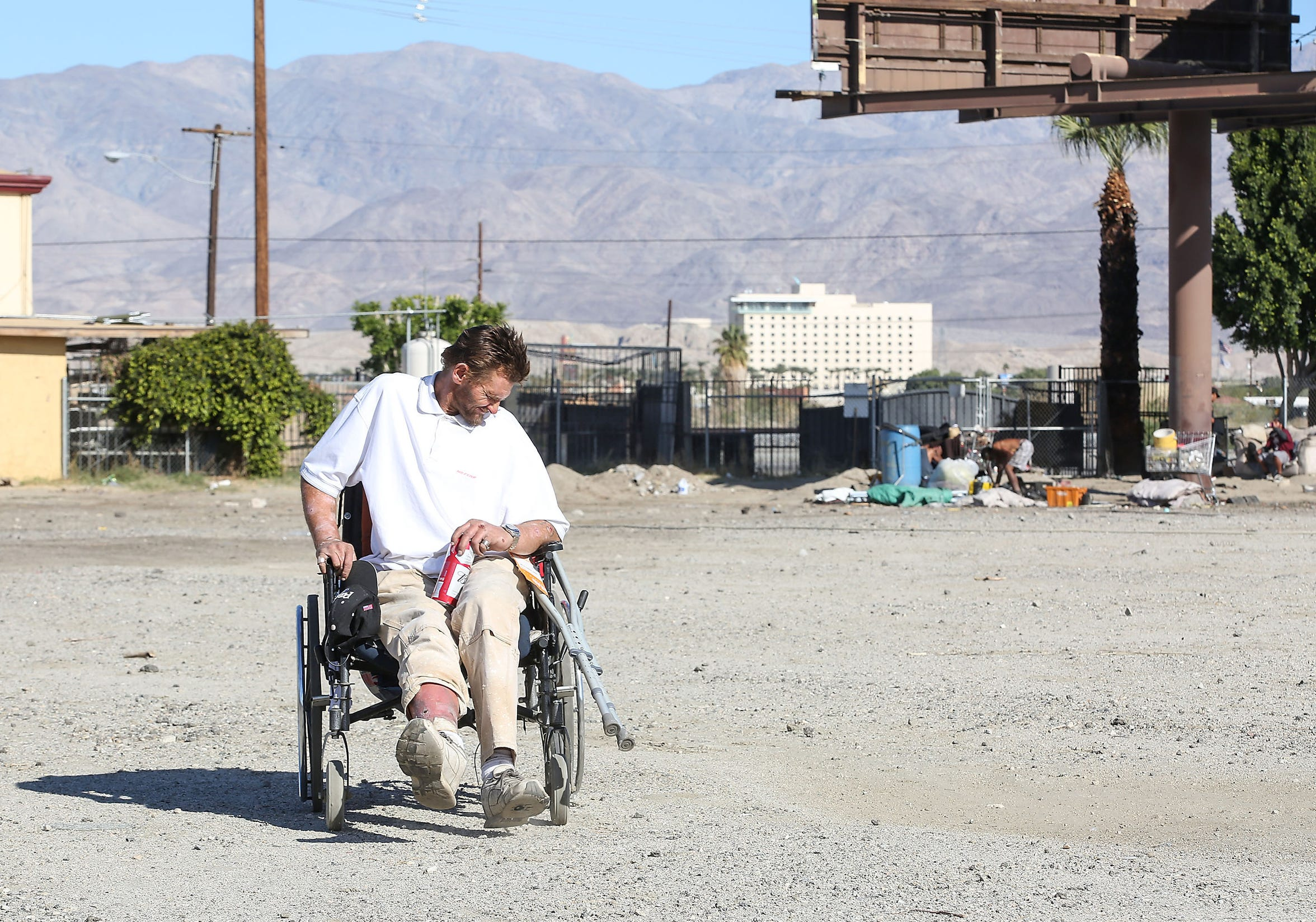 Robert Hensley pushes himself with one foot in his wheelchair.  He was hit by a car three years ago.