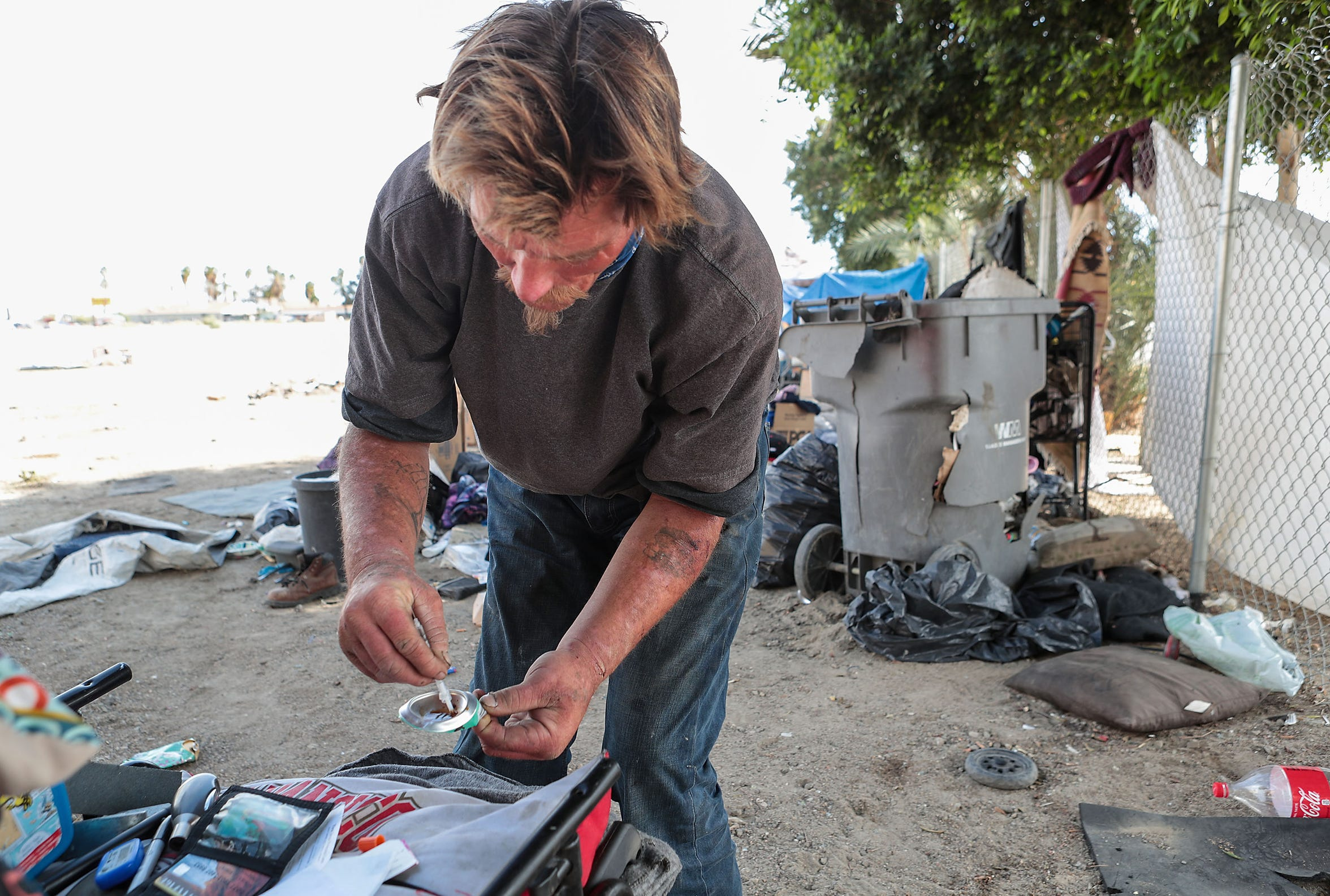 Robert Hensley prepares heroin using the bottom of an aluminum can and a syringe in Indio, April 8, 2019.