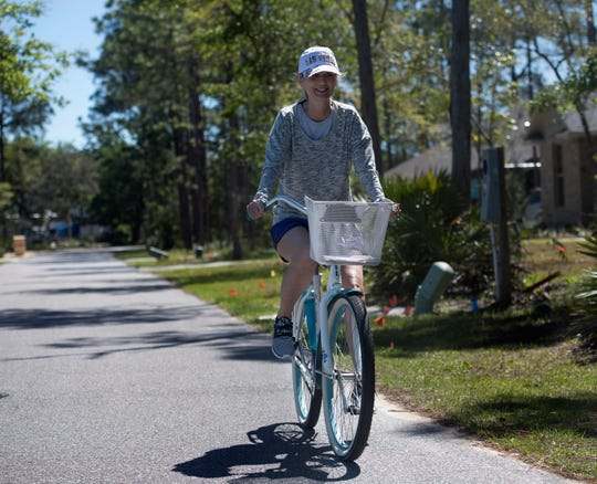Clareesa Thomas rides her bike Tuesday through her neighborhood on Innerarity Island. The Kentucky resident bought a second home on the island about a year ago and says she enjoys the tranquility it offers.