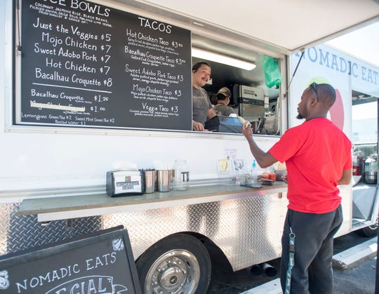 Poppy Garcia, left, takes Marcus Moultrie's order at the Nomadic Eats food truck on Tuesday along East Gregory Street in downtown Pensacola.