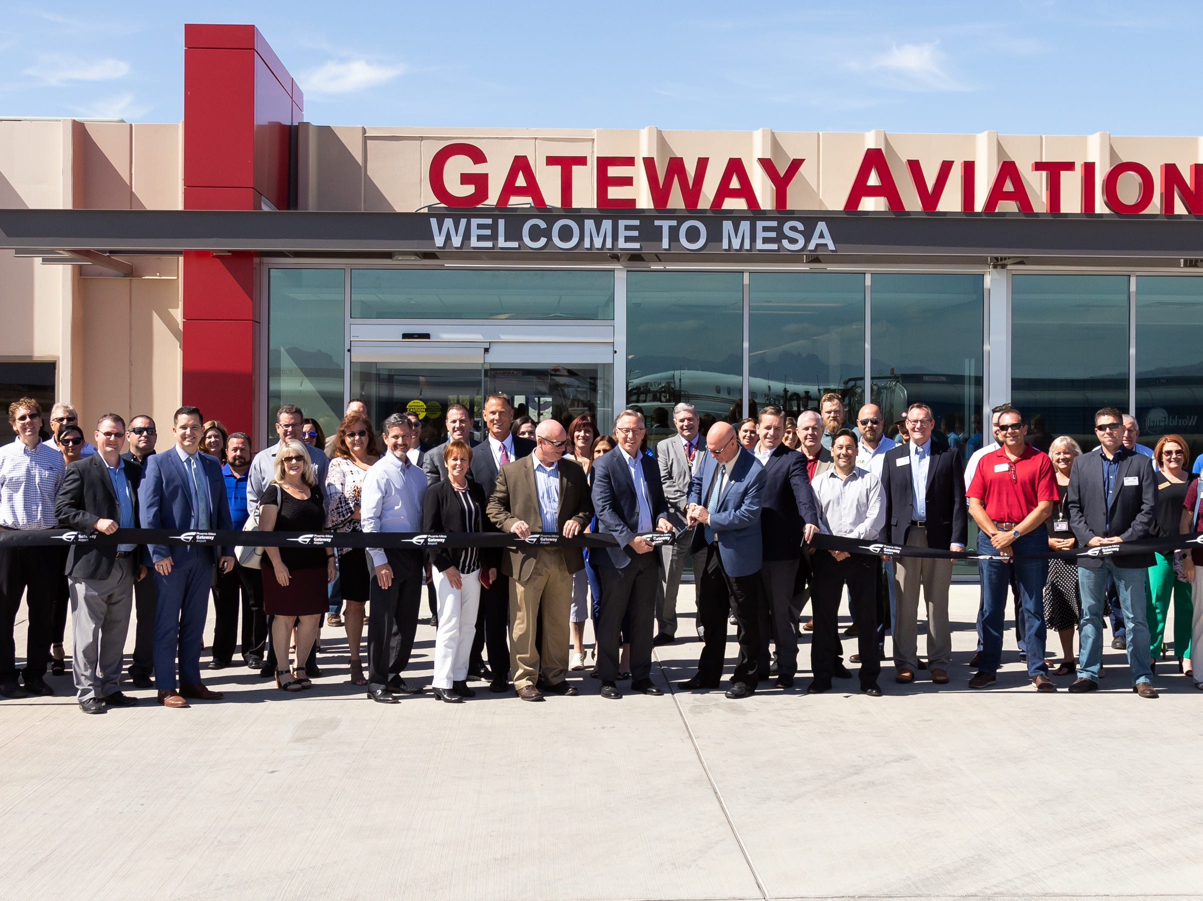 Apache Junction Mayor Jeff Serdy cuts the ribbon with Mesa Mayor John Giles at the renovated Gateway Aviation Center at Phoenix-Mesa Gateway Airport.