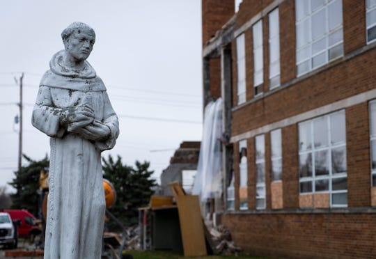 A statue of St. Francis stands on the grounds of St. Catherine's School, near where crews are working to demolish the building in Algonac.
