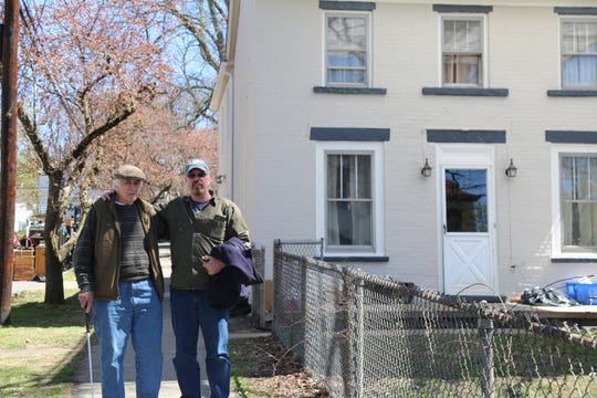 "Joseph Walsh (left) stands with his son Kevin Walsh in front of his house, where he's lived for the past 30 years, Tuesday, April 16, 2019. The house is being used as a set for an HBO limited series ""I Know This Much is True."""